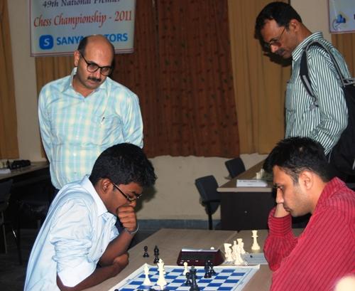 Former world u16 champion SP Sethuraman (left) against GM Tejas Bakre. Former champion GM Pravin Thisay and IM Koshy are watching.