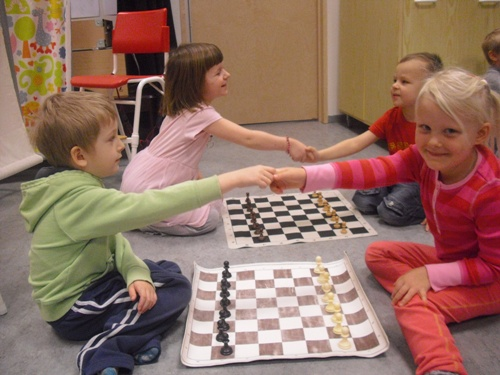 Young kids playing chess in Kindergarten
