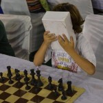 I am covering my emotions - player covers his face with chess clock box