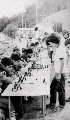 "Simultaneous exhibition by WIM Eva Kondou at the central square of Aghios Kirykos back in 1984. The legendary Greek  champion from Santorini is taking part again this year in ""Ikaros"" and is one of the favorites for the title of female Aegean Champion 2013!"