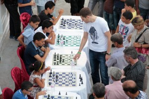 GM Kirill Stupak, giving simultaneous exhibition in this photo, is leader of the Belarus Chess Championship