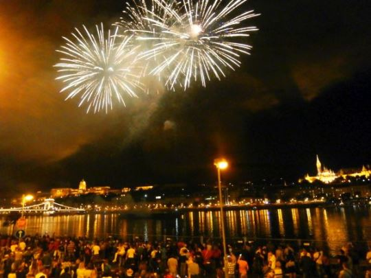 Fireworks over the Danube with glimpses of the Budapest castle and St Matthias Church on the Buda side