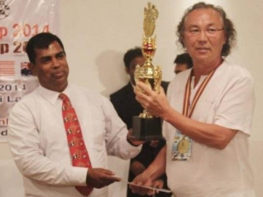 Baimurzin Aitkazy receives the trophy from L Wijesuriya