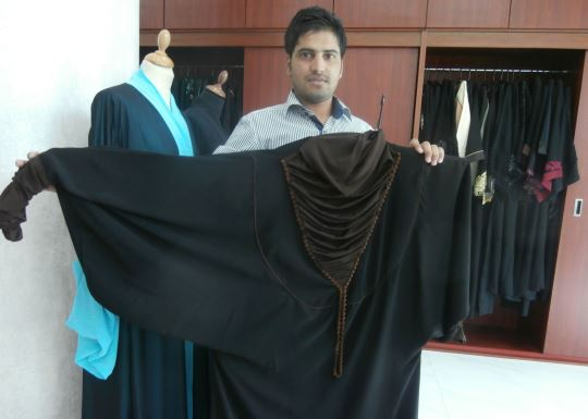 A shop assistant is displaying a handmade dress, Emirati fashion