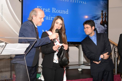 The tournament organizer Stuart Conquest helping Miss Gibraltar with the drawing of lots for Hikaru Nakamura